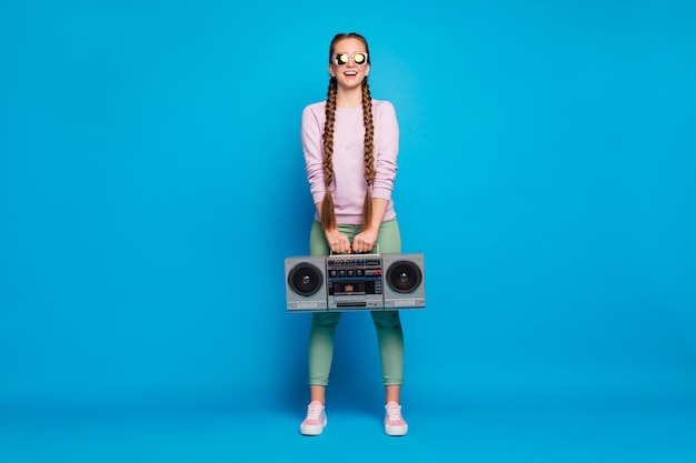 Pełne zdjęcie pozytywnego wesołego młodzieńca z warkoczami dziewczyna trzyma kasetę magnetofonową boombox chce imprezę retro na odpoczynek relaks w różowym swetrze trampki odizolowane na niebieskim tle