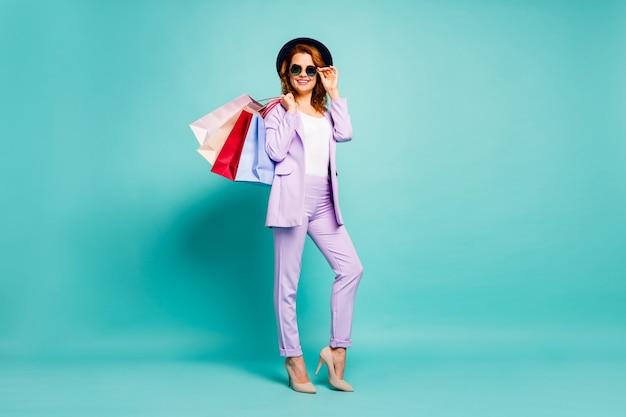 Pełne zdjęcie pozytywnej kobiety trzymającej torby w sklepie z okazją