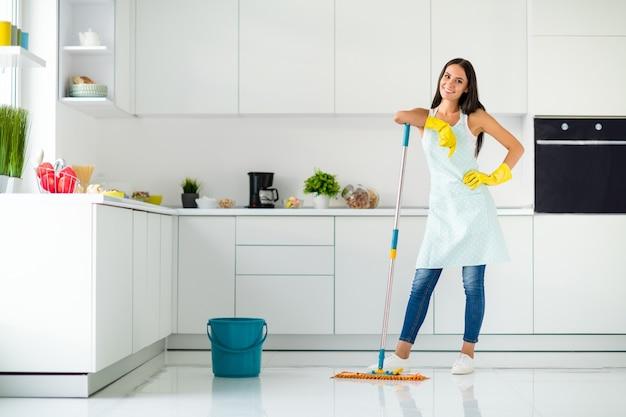 Pełne zdjęcie pozytywnej, wesołej gospodyni domowej w żółtych gumowych rękawiczkach lubiącej mycie podłogi trzymaj mop uczucie zadowolenia z noszenia dżinsów na co dzień dobrze wyglądająca odzież w domu w pomieszczeniach