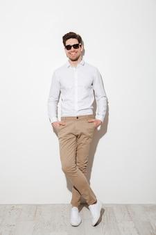 Pełne zdjęcie przystojnego faceta ubranego w swobodną odzież i okulary przeciwsłoneczne, uśmiechającego się, stojącego z rękami w kieszeniach i patrzącego przed kamerą, na białej ścianie z cieniem