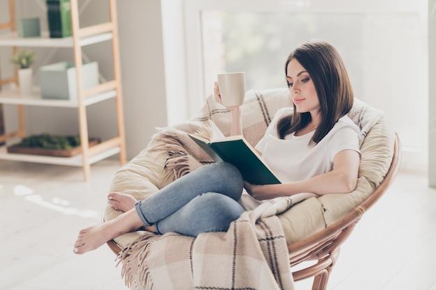 Pełne zdjęcie skoncentrowanej dziewczyny siedzi na wiklinowym krześle, czyta książkę trzymaj filiżankę kawy w nowoczesnym pokoju domowym