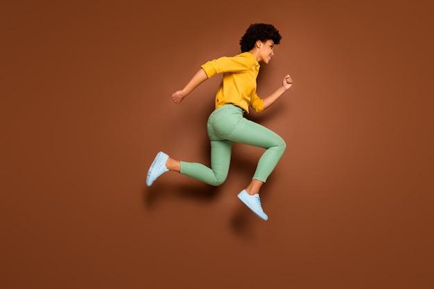 Pełne zdjęcie śmiesznej ciemnej skóry pani podskakującej w pośpiechu centrum handlowego z rabatem czarny piątek nosić żółtą koszulę zielone spodnie obuwie na białym tle brązowy kolor