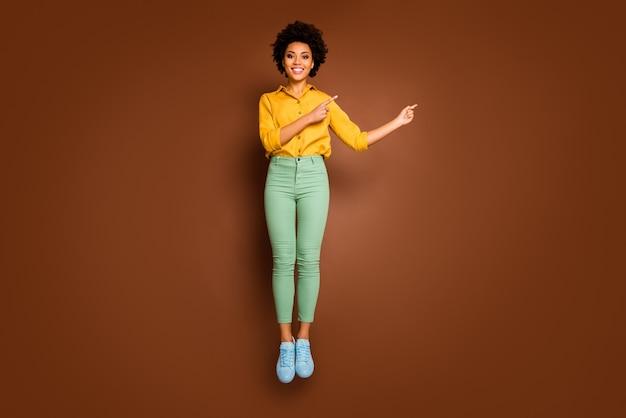 Pełne zdjęcie śmiesznej ciemnej skóry pani skacze wysoko w górę kierując palce puste miejsce niskie ceny odzież na zakupy żółta koszula zielone spodnie obuwie na białym tle brązowy kolor