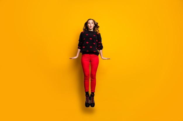 Pełne zdjęcie śmiesznej pani podskakującej wysoko, spędzającej wolny czas weekendowy, radując się, nosić sweter w serduszka, czerwone spodnie, obuwie