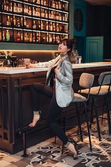 Pełne zdjęcie stockowe niezwykle modnej luksusowej brunetki w crop top, srebrnej błyszczącej kurtce, czarnych spodniach i szpilkach. model w modnym stroju siedzi na stołku barowym w klubie lub barze.