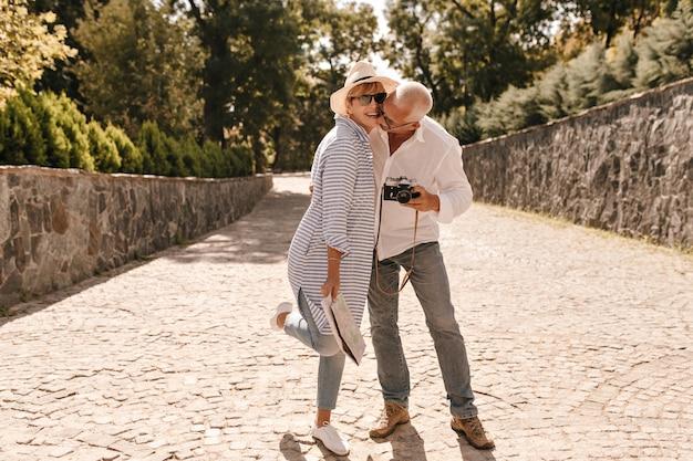 Pełne zdjęcie stylowej kobiety w kapeluszu, okularach przeciwsłonecznych i długiej niebieskiej bluzce, śmiejącej się z siwym mężczyzną w białej koszuli i dżinsach z aparatem na zewnątrz.