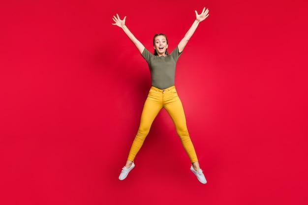 Pełne zdjęcie szalonej tysiącletniej kobiety skaczącej wysoko spędzającej wolny czas podekscytowany wesoły nastrój ubranie na co dzień żółte spodnie zielona koszulka na białym tle czerwony kolor tło