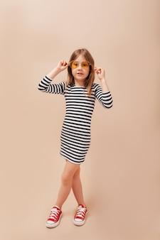 Pełne zdjęcie szczęśliwej dziewczynki w sukience w paski i okrągłych stylowych okularach bawi się na odosobnionym beżowym tle