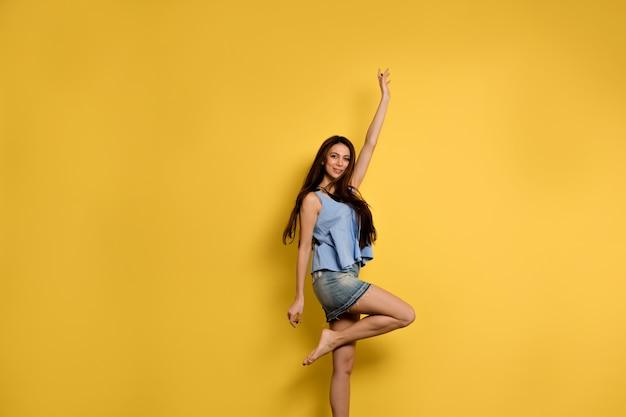 Pełne zdjęcie szczęśliwej wychodzącej kobiety w niebieskiej koszulce i dżinsowej spódniczce skaczącej z uśmiechem