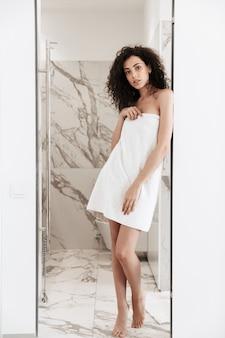 Pełne zdjęcie szczupłej, pięknej kobiety o długich ciemnych włosach w białym ręczniku, stojącej w łazience po prysznicu w pokoju hotelowym
