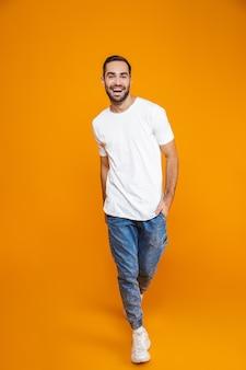 Pełne zdjęcie uroczego faceta lat 30. w t-shirt i dżinsach, uśmiechając się stojąc, odizolowane