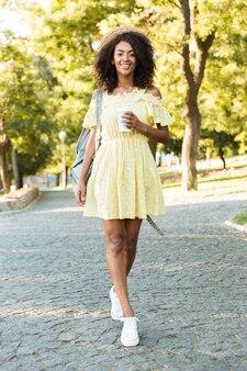 Pełne zdjęcie uroczej amerykańskiej kobiety w wieku 20 lat w słomkowym kapeluszu i sukience, spacerującej na świeżym powietrzu i trzymającej kawę na wynos