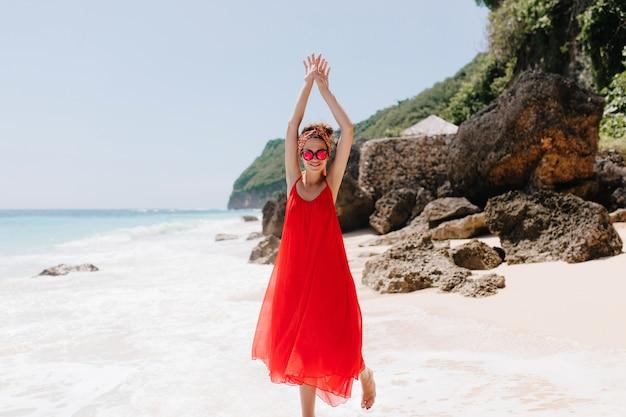 Pełne zdjęcie uroczej kobiety w długiej czerwonej sukience zabawnie tańczącej na piaszczystej plaży. zainspirowana dziewczyna w różowych okularach przeciwsłonecznych wygłupia się podczas odpoczynku w egzotycznym kurorcie.