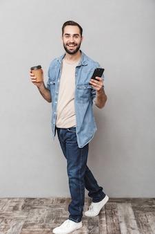Pełne zdjęcie uśmiechniętego kaukaski mężczyzna z brodą za pomocą smartfona i pijącego kawę na wynos na białym tle nad szarą ścianą
