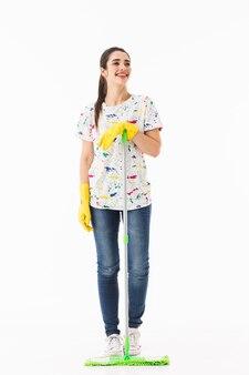 Pełne zdjęcie uśmiechniętej gospodyni domowej w wieku 20 lat w żółtych gumowych rękawiczkach do ochrony rąk myjących podłogę mopem izolowanym na białej ścianie