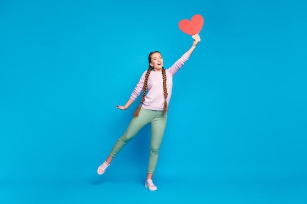 Pełne zdjęcie wesołej dziewczyny młodzieżowej z warkoczykami warkoczykami trzymać rękę łapać latającą papierową kartkę serce niespodzianka na 14 lutego nosić różowy sweter zielony stylowe spodnie na białym tle niebieski kolor tła