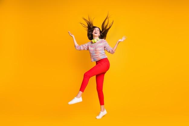 Pełne zdjęcie wesołej podekscytowanej dzikiej dziewczyny trzymającej rękę ciesz się kroplami deszczu latającej fryzury spójrz w górę copyspace nosić sweter czerwone spodnie spodnie odizolowane na jasnożółtym kolorze