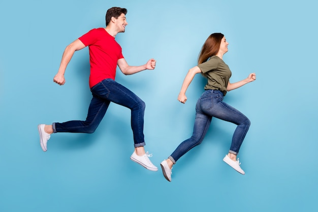 Pełne zdjęcie z profilu z boku wesołej podekscytowanej pary biegnij w pośpiechu na letnie wyprzedaże nosić zielony czerwony t-shirt dżinsy trampki izolowane na niebieskim tle