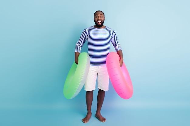 Pełne zdjęcie zabawnego ciemnoskórego faceta trzymającego dwa zielone różowe boje ratunkowe gotowego do pływania ocean morze nosić marynarską koszulę w paski białe szorty na białym tle niebieski kolor ściana