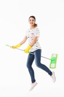Pełne zdjęcie zabawnej gospodyni domowej w wieku 20 lat w żółtych gumowych rękawiczkach do ochrony rąk, bawiącej się podczas mycia podłogi mopem na białym tle nad białą ścianą