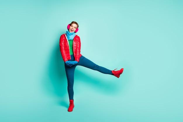 Pełne zdjęcie zabawnej pani zimowy dzień spacer ulicą spędzać najlepszy wolny czas podnosić nogę wysokie zużycie dorywczo czerwony płaszcz szalik rękawiczki różowe nauszniki spodnie buty izolowany turkusowy kolor ściana