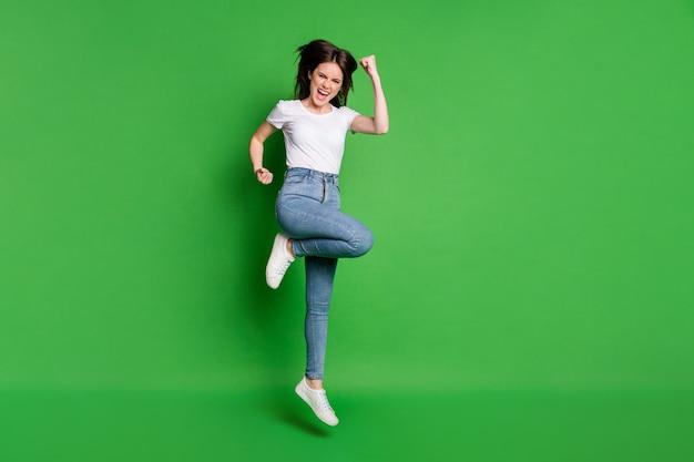 Pełne zdjęcie zachwyconej dziewczyny skaczącej, unoszącej pięść, krzyczącej tak, odizolowanej na zielonym, żywym kolorze tła