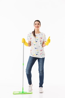 Pełne zdjęcie zadowolonej gospodyni domowej w wieku 20 lat w żółtych gumowych rękawiczkach do ochrony rąk myjących podłogę mopem izolowanym na białej ścianie