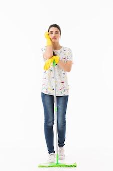 Pełne zdjęcie zdenerwowanej gospodyni domowej w wieku 20 lat w żółtych gumowych rękawiczkach do ochrony rąk myjących podłogę mopem izolowanym na białej ścianie