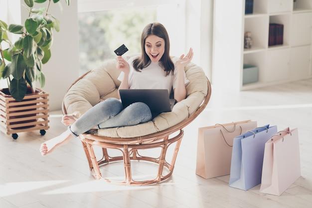 Pełne zdjęcie zdziwionej dziewczyny siedzi na krześle, wygląda na monitor laptopa, trzymaj kartę kredytową w domu, w domu, na zakupy, na zakupy, koncepcja sprzedaży