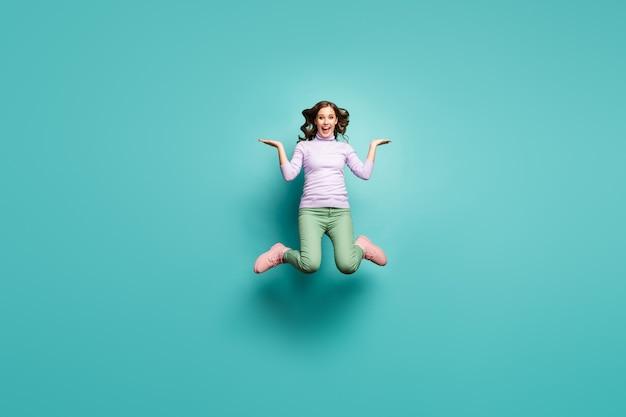 Pełne zdjęcie zwariowanej pani skaczącej wysoko trzymaj otwarte ramiona z produktami z wyprzedaży proponujące niskie ceny zakupów nosić fioletowy sweter zielone spodnie obuwie izolowany turkusowy pastelowy kolor