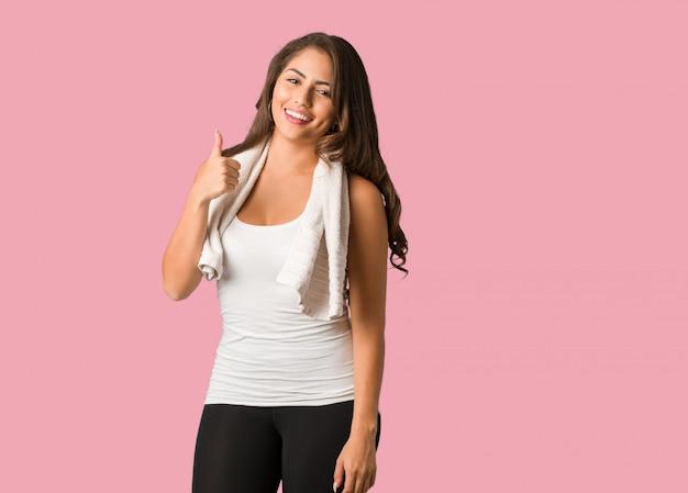 Pełnej ciała młodej sprawności fizycznej curvy kobieta uśmiecha się kciuk up i podnosi