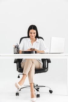 Pełnej długości atrakcyjna młoda bizneswoman siedzi przy biurku na białym tle nad białą ścianą, przy użyciu telefonu komórkowego
