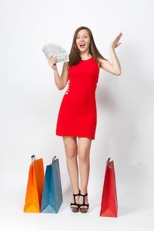 Pełnej długości atrakcyjny glamour modne młoda kobieta w czerwonej sukience gospodarstwa dolarów gotówki, multi kolorowe pakiety z zakupami po zakupach na białym tle. skopiuj miejsce na reklamę