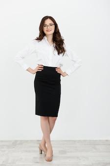 Pełnej długości biznes kobieta stoi uśmiechnięty na białym tle