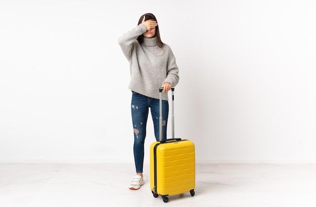Pełnej długości ciało kobiety podróżnika z walizką na odosobnionej białej ścianie zasłaniającej oczy rękami