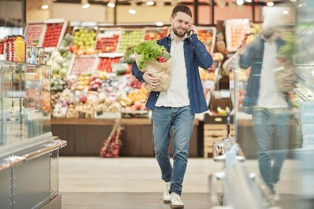 Pełnej długości dorosły, brodaty mężczyzna dzwoni przez smartfona podczas zakupów w supermarkecie