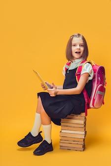 Pełnej długości emocjonalna uczennica siedzi na stosie książek, pracuje nad koncepcją edukacji dzieci na tablecie