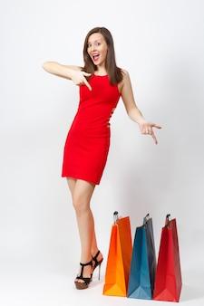 Pełnej długości glamour kaukaski młoda kobieta brązowe włosy w czerwonej sukience wskazując palcami w dół, trzymając wielokolorowe pakiety z zakupów zakupy na białym tle. skopiuj miejsce na reklamę