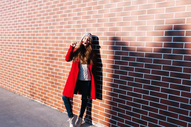 Pełnej długości ładna brunetka dziewczyna w czerwonym płaszczu na słońcu na ścianie na zewnątrz. nosi dzianinową czapkę, oblizuje usta w czerwonym lizaku, ma zamknięte oczy.