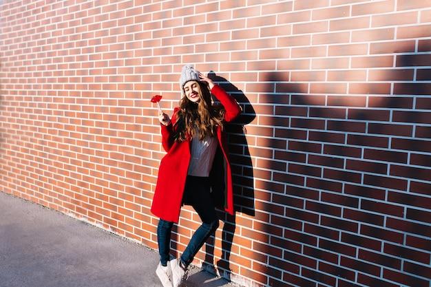 Pełnej długości ładna brunetka dziewczyna z długimi włosami w czerwonym płaszczu chłodzi w słońcu na ścianie na zewnątrz. nosi dzianinową czapkę, trzyma usta w kształcie lizaka, ma zamknięte i uśmiechnięte oczy.