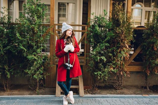 Pełnej długości ładna dziewczyna z długimi włosami w czerwonym płaszczu i czapce stojącej na drewnianym domu. trzyma aparat i kawę w białych rękawiczkach, uśmiechając się w bok.