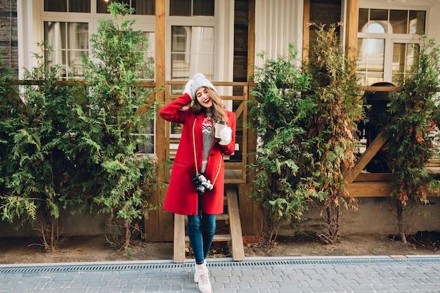 Pełnej długości ładna dziewczyna z długimi włosami w czerwonym płaszczu i czapce stojącej na drewnianym domu. trzyma aparat i kawę w białych rękawiczkach. wygląda na zadowolonego z zamkniętymi oczami.