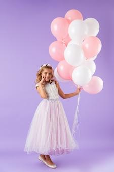 Pełnej długości ładna dziewczynka ubrana w sukienkę księżniczki, stojąca na białym tle nad fioletową ścianą, trzymająca balony