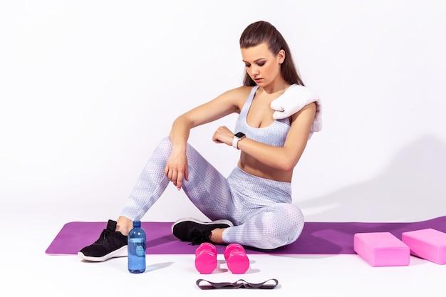 Pełnej długości lekkoatletyczna brunetka kobieta w białej sportowej bluzce i rajstopach siedzi na macie do jogi, patrząc na jej monitor fitness, sprawdzając wskaźniki po treningu. kryty studio strzał na białym tle na szarym tle