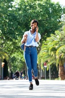 Pełnej długości młoda afrykańska kobieta opowiada i chodzi z telefonem komórkowym