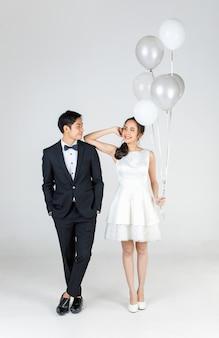 Pełnej długości młoda atrakcyjna para azjatyckich, panna młoda i pan młody, kobieta ubrana w białą suknię ślubną, trzymając balon. mężczyzna ubrany w czarny smoking, stojący razem. koncepcja fotografii przedślubnej.