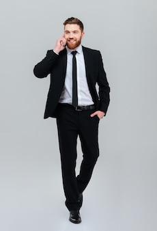 Pełnej długości młody brodaty człowiek biznesu w czarnym garniturze porusza się z ręką w kieszeni i rozmawia przez telefon w studio na białym tle szarym tle