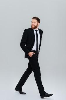 Pełnej długości młody brodaty człowiek biznesu w czarnym garniturze porusza się z rękami w kieszeniach w studio i patrząc wstecz widok z boku na białym tle szarym tle