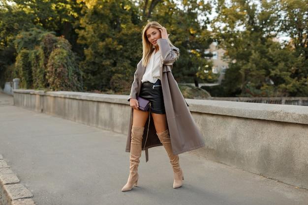 Pełnej długości moda wizerunek eleganckiej blond kobiety w stylowym luksusowym beżowym skórzanym płaszczu i wysokich obcasach, spacery na świeżym powietrzu