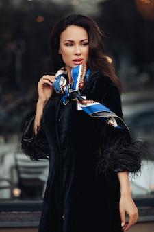 Pełnej długości modna dama w czarnym płaszczu i skórzanych butach z kolorową chusteczką na szyi. niesie filiżankę kawy na wynos przed otwartym samochodem na ulicy.